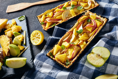 delicious pineapple and apple sweet tart in Rectangular Tart Pans on a concrete table with kitchen towel and ingredients, horizontal view from above, close-up Stock Photo