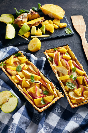 delicious pineapple and apple sweet tart in Rectangular Tart Pans on a concrete table with kitchen towel and ingredients, vertical view from above