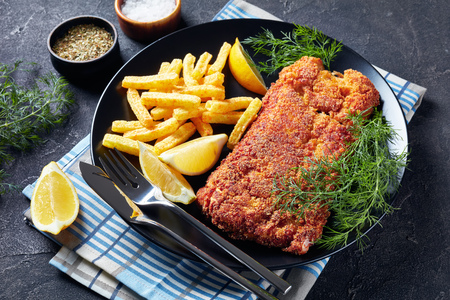 close-up of Breaded hake fillet served with chips, fresh dill and lemon slices on a black plate on a concrete table, horizontal view from above