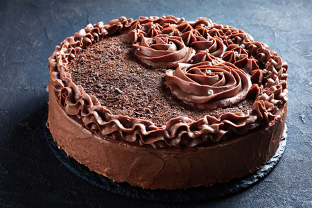 close-up of a chocolate meringue festive Cake topped with Chocolate buttercream roses and silver edible dragee, horizontal side view from above, macro Stok Fotoğraf - 122613226