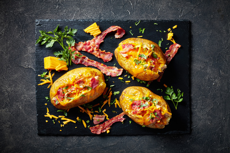 Loaded freshly Baked Potatoes with Bacon, pulled chicken breast and Cheddar on a black slate plate on a concrete table, horizontal view from above, close-up, flatlay