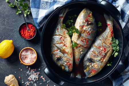 Raw dorado fishies marinated with spices, sea salt, ginger, soy sauce and herbs in a baking dish on a concrete table with ingredients, view from above, flatlay
