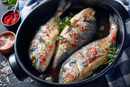 three Raw dorado fish marinated with spices, sea salt, ginger, soy sauce and herbs in a baking dish on a concrete table with ingredients, view from above, close-up Stock Photo