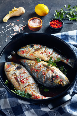 three Raw dorado fish marinated with spices, sea salt, ginger, soy sauce and herbs in a baking dish on a concrete table with ingredients, vertical view Stock Photo