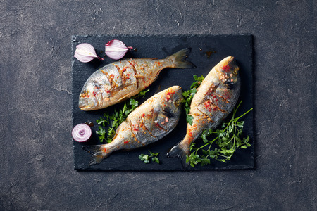 three Raw dorado fish prepared to cook with spices, sea salt, parsley, and red onion on a black stone tray on a concrete table, view from above, flatlay, copy space Standard-Bild