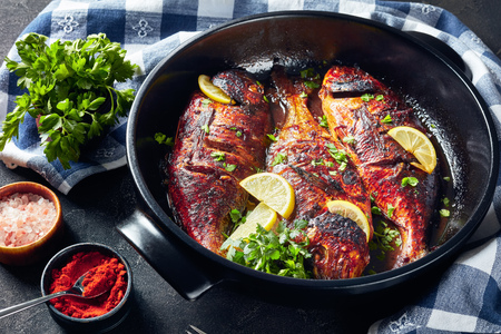 delicious freshly grilled dorado fish in a black ceramic baking dish on a concrete table with a kitchen towel and parsley, view from above Standard-Bild