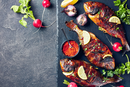 delicious freshly grilled dorado fish served on a black slate tray with radish, lemon slices on a concrete table, horizontal view from above, copy space, flatlay, close-up Stock Photo