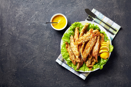 Fried in batter capelins served on a bed of fresh lettuce leaves with sliced lemon on a plate on a concrete table with orange mustard sauce, fork and knife, view from above, flatlay, copy space