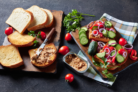 close-up of toasts with Cod Liver pate, topped with sliced cucumber, tomatoes and red onion rings on a cutting board with ingredients on a kitchen table, view from above Banco de Imagens