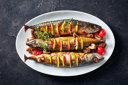 close-up of three whole broiled mackerels with lemon, tomatoes, mushrooms, spices and herbs on a white oval dish, horizontal view from above, flatlay,