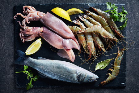 sea bass, king prawns, calamari, lemon slices, spices and herbs on a slate plate on a concrete table, view from above, close-up, flatlay
