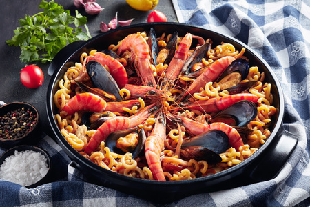 Spanish Fideua, a noodle Paella with seafood - king prawns, white fish meat, calamari, mussels in a black pan on a concrete table with ingredients, horizontal view from above, close-up