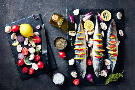 three whole raw mackerel with lemon, tomatoes, mushrooms, spices and herbs. scomber on a stone tray on a concrete table with ingredients view from above, flatlay