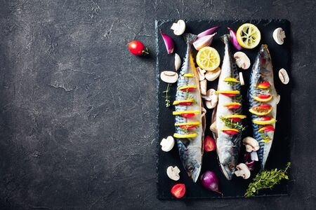 three whole raw mackerel with lemon, tomatoes, mushrooms, spices and herbs. scomber on a stone tray on a concrete table, view from above, flatlay, empty space