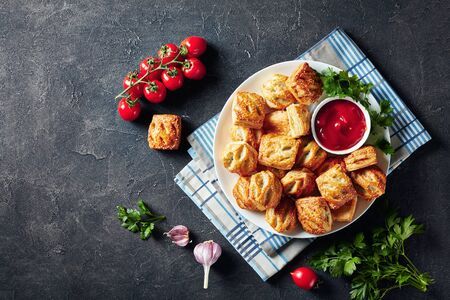overhead view of freshly baked Puff pastry rolls with minced chicken meat  and mushrooms served with ketchup and parsley on a white plate on a concrete table, view from above, flatlay, copy space