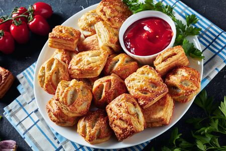 Puff pastry buns with minced chicken meat  and mushrooms served with ketchup and parsley on a white plate on a concrete table, view from above