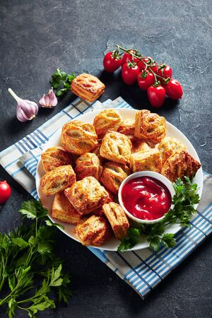 Puff pastry rolls with minced chicken meat  and mushrooms served with ketchup and parsley on a white plate on a concrete table, vertical view from above