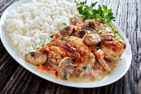 chicken stewed with cream white wine sauce, mushrooms and vegetables and served with rice on a plate on a dark wooden  table -  Fricassee de Poulet, classic french recipe,, close-up