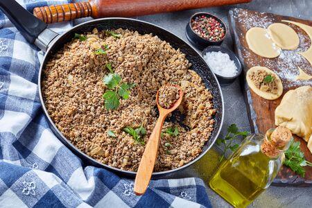 Hígado molido con cebolla frita en una sartén, ingrediente de relleno para pierogies, masa cruda y bola de masa cruda en un bord de corte con rodillo en el fondo, vista desde arriba, primer plano