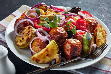 close-up of freshly roasted in an oven hot vegetables - potatoes, eggplants, zucchini, tomatoes, bell peppers on a white platter on a grey concrete table, horizontal view from above Banco de Imagens - 125291953