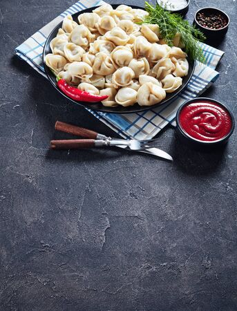 Delicious hot dumplings with ground beef filling served on a black plate with dill and tomato sauce, vertical view from above