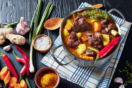 Jamaican Curried Goat – slow cooked Jamaican Spiced goat Curry in a pot on a black wooden table with ingredients on a cutting board, view from above Banque d'images