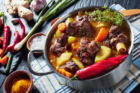 close-up of Jamaican Curried Goat – slow cooked Jamaican Spiced goat Curry in a pot on a black wooden table with ingredients on a cutting board, horizontal view from above