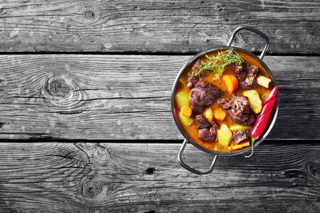 overhead view of traditional Jamaican Curry Goat – slow cooked Jamaican Spiced meat and vegetables spicy Curry in a pot on a rustic wooden table, view from above, flat lay, copy space