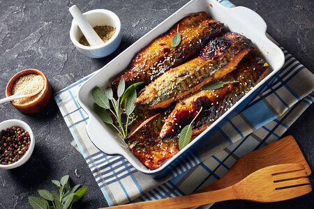 delicious roasted fillets of mackerel fish in a baking dish on a concrete table with spices at the background, view from above Stock Photo