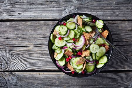 summer cucumber salad with red currant, marinated red onion and crisp flatbread pieces in a black bowl on a rustic wooden table, copy space, flatlay