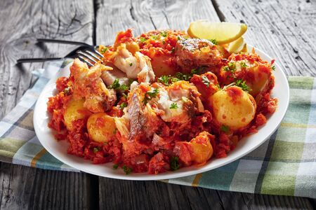 close-up of hake fish stew with new potatoes and carrot onion tomato sauce served on a white plate with lemon wedges, view from above Stock Photo