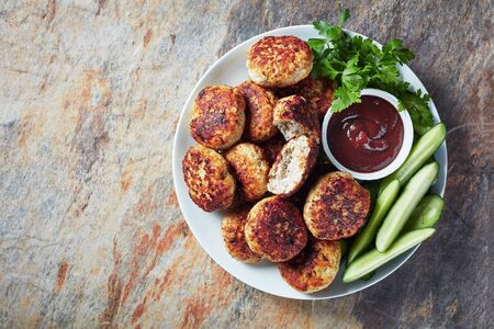 Polish Meat rissoles served with cucumber slices and barbecue sauce on a white plate on a table, horizontal view from above, flat lay