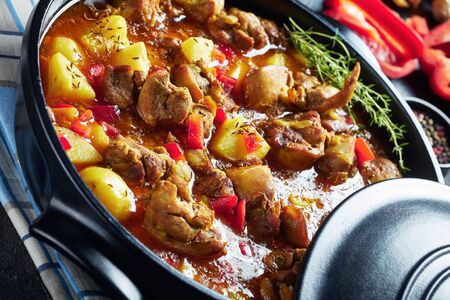 Close-up of chicken curry with potato, bell pepper, spices in a black ceramic pan Reklamní fotografie