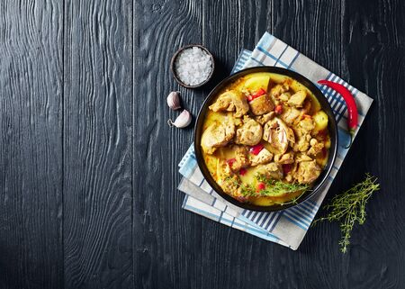Close-up of chicken curry with potato, finely chopped red bell pepper, spices in a black bowl on a wooden table