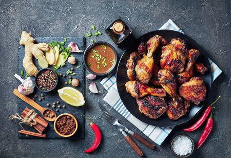 Spicy Grilled Caribbean Jerk Chicken drumsticks and thighs on a black platter on a concrete table with ingredients on a stone board Reklamní fotografie
