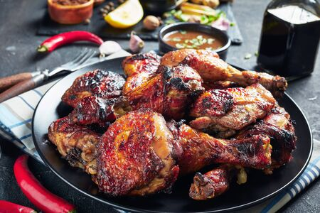 close-up of hot Grilled Jamaican Jerk Chicken drumsticks and thighs on a black plate on a concrete table with ingredients at the background, horizontal view from above