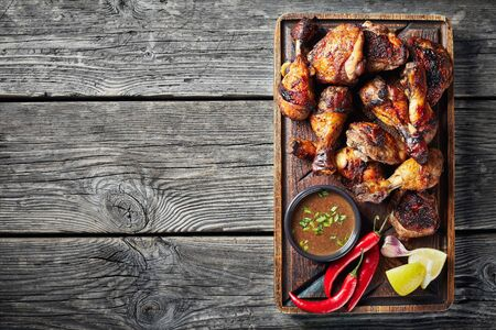 overhead view of Jerk Chicken on a rude board with sauce and lemon on a rustic wooden table