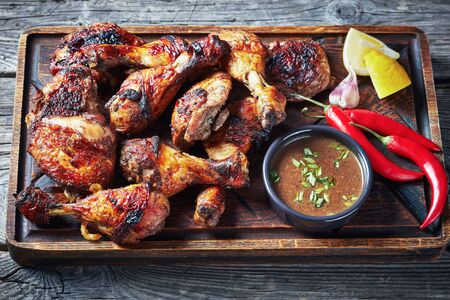 hot Grilled Jamaican Jerk Chicken on a rude board with sauce and lemon on a rustic wooden table