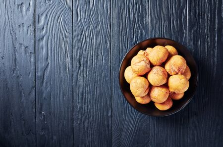 Caribbean fried unleavened dumplings in a black bowl on a wooden table, horizontal view from above, flat lay Reklamní fotografie