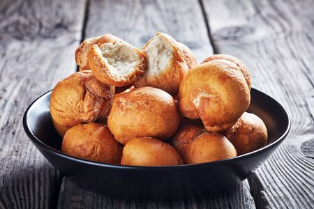 Caribbean fried dumplings in a black bowl on an old wooden rustic table, close-up Reklamní fotografie