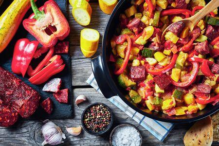 Pisto manchego - stufato di verdure con salsicce chorizo in una padella nera su un tavolo di legno rustico con ingredienti sul tagliere, cucina spagnola, vista dall'alto, flatlay, primo piano