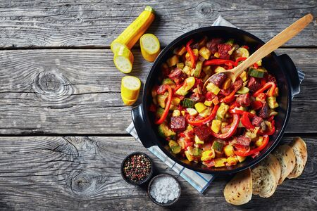 overhead view of Pisto manchego - vegetable stew with chorizo sausages in a black pan on a rustic wooden table, spanish cuisine, view from above, flatlay, close-up