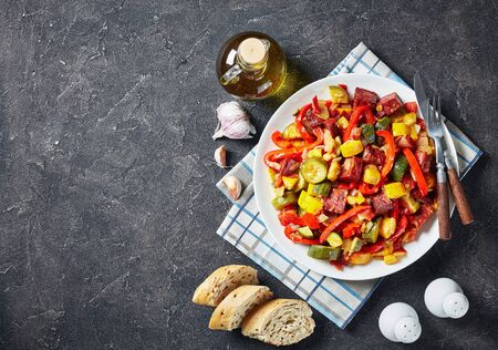 Pisto manchego - Spanish vegetable stew with fried chorizo sausages served on a white plate on a concrete table with sliced bread, view from above, close-up, flatlay Reklamní fotografie