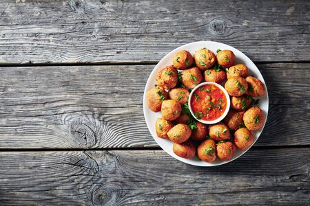 Plantain fritters Klako on a white plate with hot sauce, vegan side dish, street food, african cuisine Reklamní fotografie