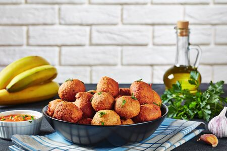 close-up of deep fried Plantain fritters Klako in a black bowl with ingredients and brick wall at the background, african cuisine, horizontal view