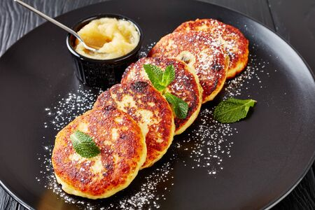 german quark Potato pancakes - Quarkkeulchen sprinkled with powdered sugar and decorated with mint leaves on a black platter with apple sauce, view from above, close-up
