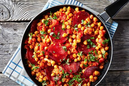 close-up of Garbanzos fritos, fried Chickpeas with chorizo, ham tomatoes and spices in a skillet