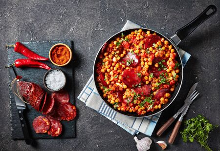 Garbanzos fritos, fried Chickpeas with chorizo, ham tomatoes and spices in a skillet on a concrete table with ingredients, spanish cuisine.