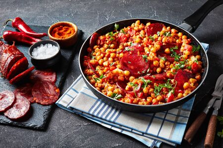 close-up of Garbanzos fritos, fried Chickpeas with chorizo, ham tomatoes and spices in a skillet on a concrete table with ingredients, spanish cuisine.