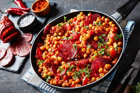 close-up of Garbanzos fritos, stewed Chickpeas with chorizo, ham, tomatoes and spices in a skillet on a concrete table with ingredients, spanish cuisine. Stok Fotoğraf
